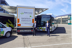 Georges Hilbert General Director Sales-Lentz and Volker Winter Sales Manager ads-tec Energy GmbH in front of the fast charging solution Mobile High Power Charger from ADS-TEC. (Photo: ADS-TEC)